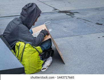 USA, Chicago, Illinois. May 9, 2019. Homeless sitting on the roadside reading a book and asking for help, downtown