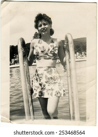 USA - CIRCA 1944: Reproduction of an antique photo shows young woman in swimsuit posing on the ladder of the ship on a background of water and shore resort