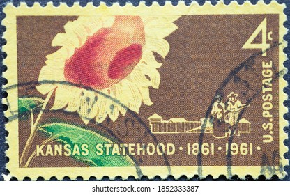 USA - Circa 1961 : a postage stamp printed in the US showing a sunflower, and a pioneer family with a covered wagon and stockade.Text: Kansas Statehood