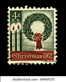 USA - CIRCA 1962:  America's first Christmas postage stamp shows a wreath and candles. It was well received and started a long tradition of a new Christmas stamp each year, circa 1962