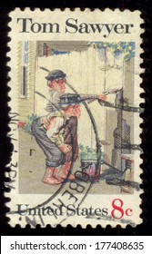 """USA - CIRCA 1972: A postage stamp printed in USA, American Folklore Issue, shows Tom Sawyer, by Norman Rockwell, circa 1972. Tom Sawyer, hero of """"The Adventures of Tom Sawyer,"""" by Mark Twain"""