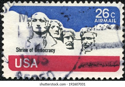 USA - CIRCA. 1974: United States postage stamp in the value of 26c showing former presidents' heads at Mount Rushmore and the print 'Shrine of Democracy', circa 1974.