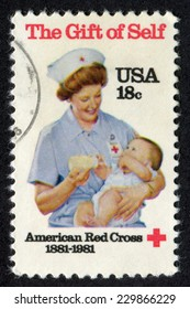 USA- CIRCA 1981: Postage stamp printed in United States of America shows a nurse feeding baby with milk. American Red Cross Centennial. Scott Catalog 1910 A1297 18c, circa 1981