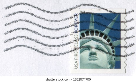 USA- CIRCA 2011: part of an envelope with a wave postmark with a postage stamp printed in the USA shows the image of the Statue of Liberty. USA FIRST CLASS FOREVER WITH HAPPY HOLIDAYS MARK circa 2011