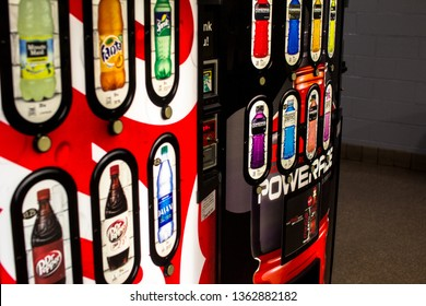 U.S.A. - CIRCA 2019: Closeup of Two Cola Soda Pop Soft Drink, Juice Beverage and Bottled Water Vending Machines with Selection Buttons showing Branded Product Labels in a lobby