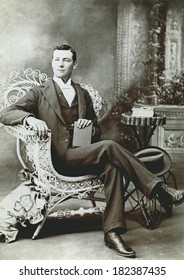USA - COLORADO - CIRCA 1895 A vintage cabinet card photo of a gentleman holding a fedora hat. He is sitting in a chair while holding a book. Photo from the Victorian era. CIRCA 1895