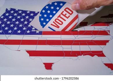 USA Wahlen 2020, die Hand eines Mannes, die seine Stimme in einem Wahlzettel mit der US-Karte und Flagge.