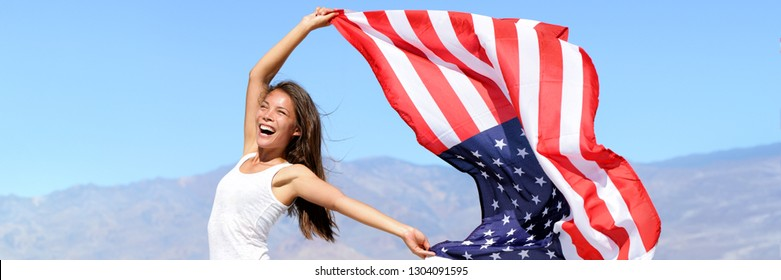 USA flag American woman waving the american flag in success. Asian girl cheering winner outdoors in summer banner panorama background. Beautiful energetic happy young model joyful excited.