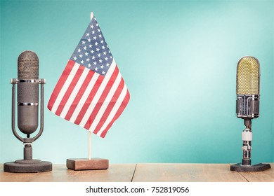 USA flag and big retro old studio microphones on wooden desk front mint green wall background. Vintage instagram style filtered photo
