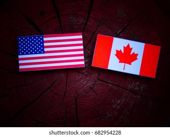 USA flag with Canadian flag on a tree stump isolated