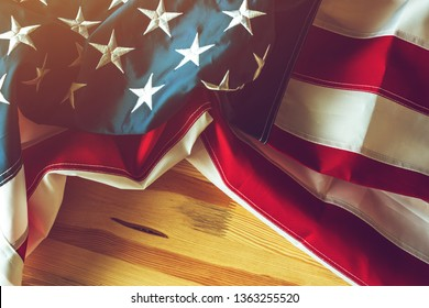 USA flag crumpled on wooden background, american banner with embroidered stars and stripes