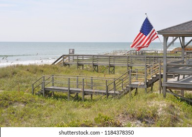 A USA flag flies proudly along a walkway to the beach and Atlantic Ocean.