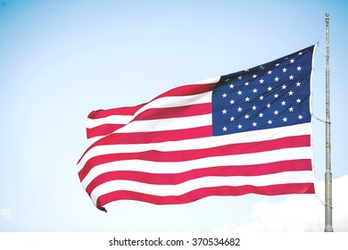 A USA flag flies in a strong wind on the blue sky in New York, USA