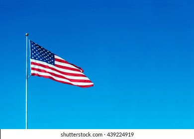 USA flag flies in a wind on blue sky background, place for your text