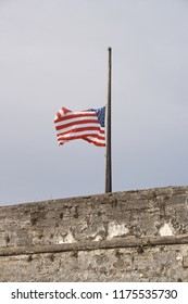 USA flag fluttering in the wind at half mast.