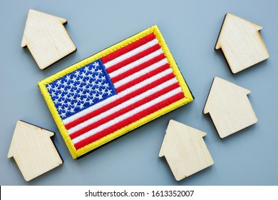 USA flag and models of house. VA direct home loan concept.
