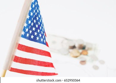 USA flag, stack of coins and dollars in background, selective focus. Travel America concept