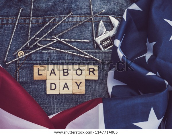 USA flag, tools, and wooden letters with the inscription LABOR DAY on the background of a blue jeans pocket. Top view, close-up. Preparation for the celebration of Labor Day