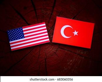 USA flag with Turkish flag on a tree stump isolated