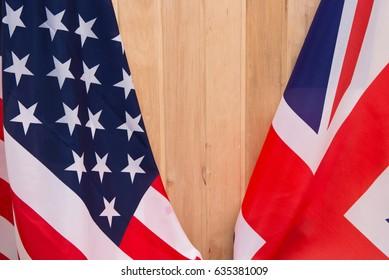 USA flag and UK Flag on wooden background light.