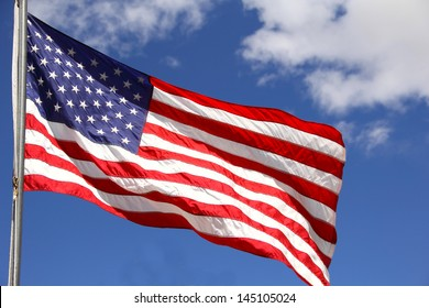 U.S.A. Flag United States of America flag.  The red, white and blue flag waving in the wind.  The background of the image is blue sky and clouds.