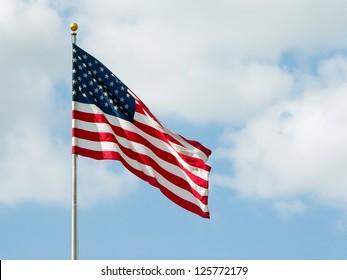 USA flag waving with a cloudy blue sky