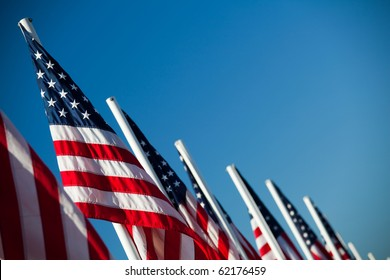 USA flags - vibrant American flags in a row under clear blue sky
