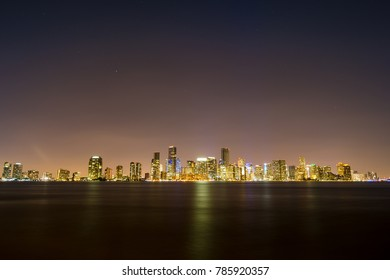 USA, Florida, Reflecting beautiful city lights of miami skyline on silent water at night with starry sky