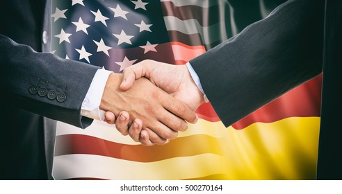 USA Germany business. Formal handshake on USA - Germany flags background
