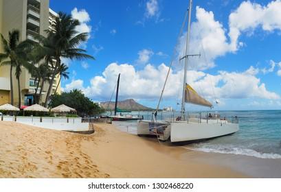 USA, HAWAII - AUGUST 31, 2018: Catamaran docked on Waikiki Beach with Diamond Head in background at in Honolulu, Hawaii