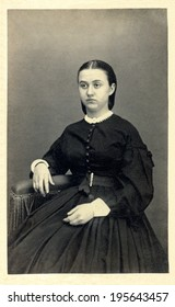 USA - ILLINOIS - CIRCA 1863 Vintage carte de visite photo of young woman sitting in chair dressed in hoop skirt dress from the nineteen century. This photo from the Civil War Victorian era. CIRCA 1863