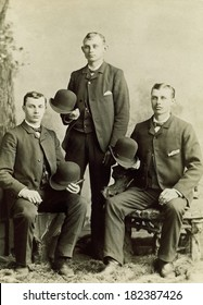 USA - ILLIONOIS - CIRCA 1890 A vintage cabinet card photo of three young gentlemen holding their derby bowler hats. Two are sitting and one is standing. Photo from the Victorian era. CIRCA 1890
