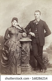USA - INDIANA - CIRCA 1885 - A vintage photo of a young couple. They are both standing. The woman is dressed in a Victorian bustle style dress. A photo from the Victorian era. CIRCA 1885