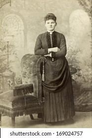 USA - INDIANA - CIRCA 1885 - A vintage antique photo of a young woman standing leaning on chair. The woman is dressed in a Victorian style dress. A photo from the Victorian era. CIRCA 1885