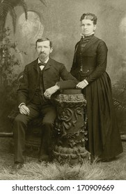 USA - KANSAS - CIRCA 1885 - A vintage photo of a young couple. The husband is sitting and the wife is standing. She is dressed in a Victorian style dress. A photo from the Victorian era. CIRCA 1885