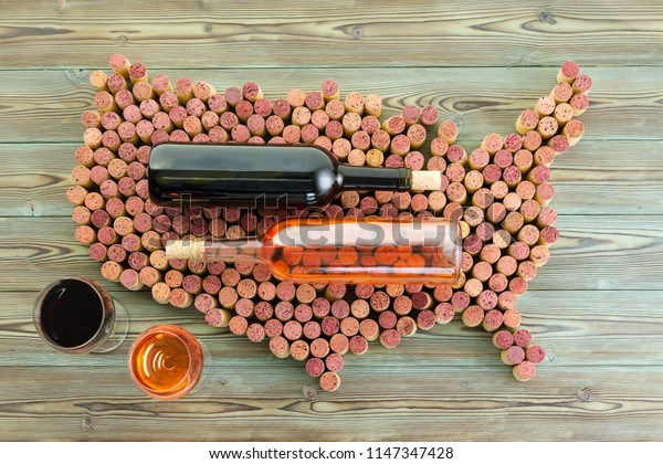 USA map formed of used red wine corks with two bottles overlaid on top and full wineglasses alongside in a creative flat lay viticulture background