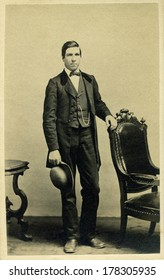 USA - MASSACHUSETTS - CIRCA 1865 - Vintage Cartes de visite photo of a young man. The man is standing  next to chair holding a derby style hat. A photo from the Civil War Victorian era. CIRCA 1865