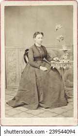 USA MASSACHUSETTS CIRCA 1870 A Vintage Carte De Visite photo of a young woman sitting in a chair. She is wearing a hoop skirt. Photo from the civil war victorian era. CIRCA 1870