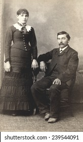 USA MICHIGAN CIRCA 1885  A Vintage Carte De Visite photo of a couple. He is sitting in a chair and she is standing. Photo from the Victorian era. CIRCA 1885