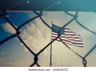 USA and migration border fence. US of America flag behind a steel wire mesh