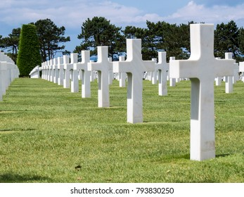 USA Military Cemetery, Colleville sur Mer, Normandy, France - 6 August 2014:   Lines of white crosses in a green grass that honors American troops who died in Europe during World War II.