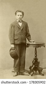 USA - MINNESOTA - CIRCA 1870 - A vintage Cartes de visite photo of a young boy standing next to a round table. He is wearing a suit, tie and derby style hat. A photo from the Victorian era. CIRCA 1870