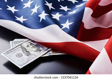 USA national flag and currency usd money banknotes on dark background. Business and finance concept