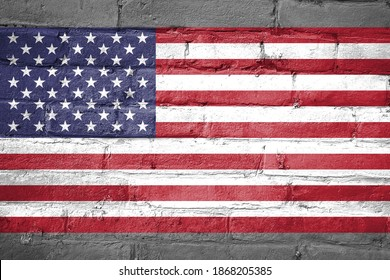 USA national flag icon painted on old weathered bricks wall background, vintage United States flag painting pattern texture wallpaper