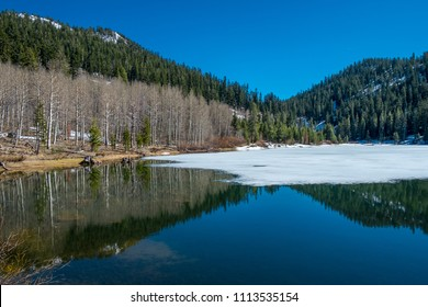 USA, Nevada, Carson City, Lake Tahoe Basin: The Sierra Mountains symmetrically reflected in the partially frozen surface of Marlette Lake.