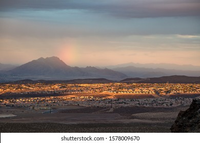 USA, Nevada, Clark County, Henderson. A sunset, sun dog rainbow, and Frenchman Mountain over the Sun City Anthem planned community neighborhood south of Las Vegas.