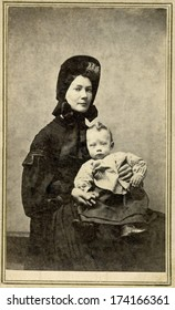 USA - NEW YORK - CIRCA 1865 - A vintage Cartes de visite photo of young woman sitting in chair holding her baby. She is dressed in hoop skirt dress.  Photo from the Civil War Victorian era. CIRCA 1865