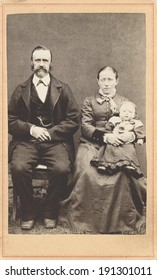 USA - NEW YORK - CIRCA 1865 A vintage Carte De Visite photo of a young pioneer family. The parents are sitting and the mother is holding baby. The photo is from the civil war Victorian era. CIRCA 1865