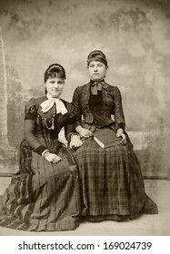 USA - NEW YORK - CIRCA 1890 - A vintage antique photo of two young women sitting in fashionable clothing. Both women are dressed in a Victorian style dress. A photo from the Victorian era. CIRCA 1890