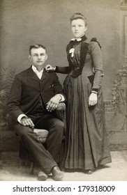 USA - NEW YORK - CIRCA 1890 A vintage Cabinet Card photo of a young couple. They are dressed in Victorian style clothing. She is standing and he is sitting. A photo from the Victorian era. CIRCA 1890